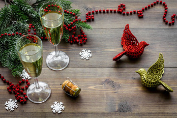 Glasses of champagne in eve of New Year 2018 near spruce branch and decoration on wooden background