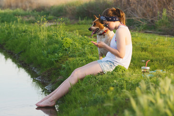 A teen girl sits on an embankment  with her dog dipping feet in the water