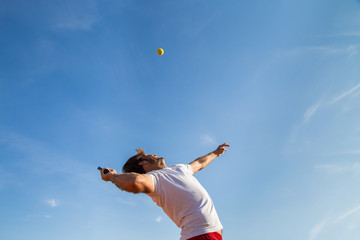 Professional tennis player throwing ball in the air before hitting it.