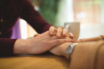 Couple holding hands while relaxing at home