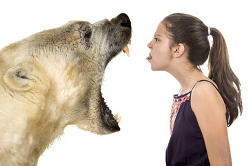 Young fearless girl with a polar bear on a white background