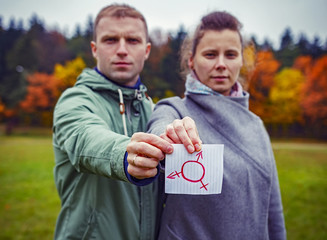 Male and female together holding piece paper with drawing transgender symbol. Human sex rights. Gender symbol in hands of man and woman