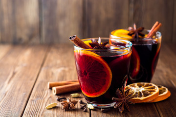 Two glasses of christmas mulled wine with oranges and spices on wooden background.