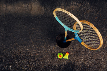 Two Old Badminton Rackets in a Copper Can and Two Birdies From Above