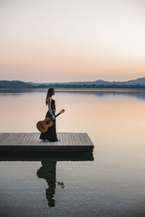 Young and free woman relaxing in the nature with a guitar
