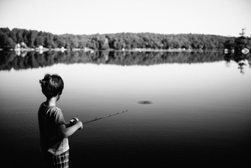 Boy casts his fishing pole into a lake