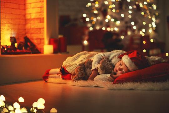 child girl fell asleep near tree on Christmas Eve