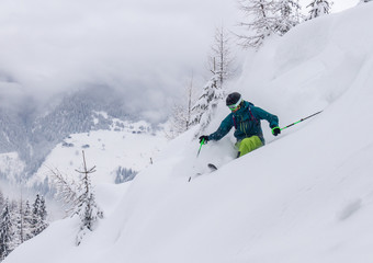 young male freerider skiing down a powder slope