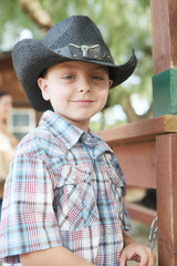 Portrait of young handsome cowboy wearing hat and plaid shirt