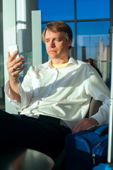 Tired businessman checking cellphone in airport terminal, resting legs up