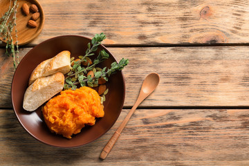 Plate with mashed sweet potato and bread on wooden background