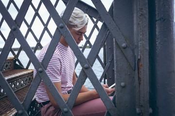 Man using mobile phone on metal stairs