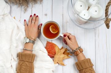 Autumn Holiday . Hands hold cup of tea on wooden table.