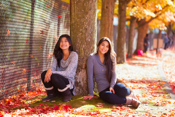 Biracial teen girl sitting under colorful maple trees in autumn
