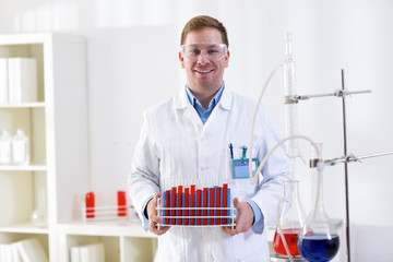 Young science holding tubes at professional lab