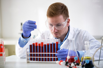 Concentrated chemist holding pipette and working at laboratory