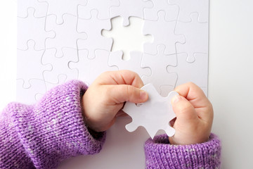 Child hands holds the last puzzle piece of a Jigsaw puzzle