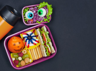 Open lunch box with Halloween school lunch near thermo mug on black background