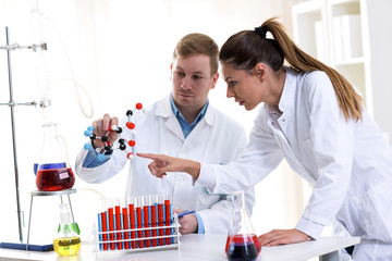 Two young chemist students researching at school lab