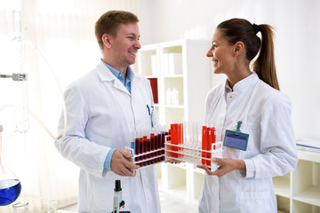 Two chemists holding tubes and talking about job