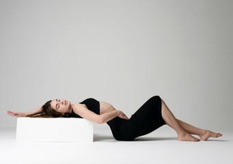 Slim beautiful brunette woman lying posing on a floor in sexy underwear bra