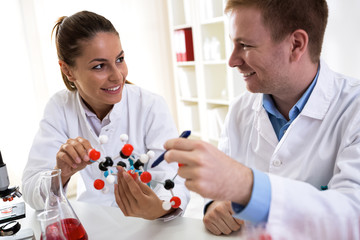 Two students of chemistry looking at molecular model and making new formula