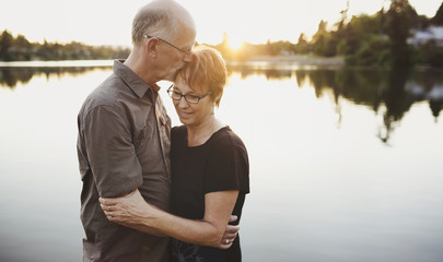 Content middle aged, retired couple hugging together outside on lake ocean dock