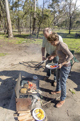 Grey nomads couple standing in front of campfire watching food cook