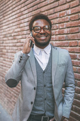Smiling cute black businessman on phone in front a brick wall.