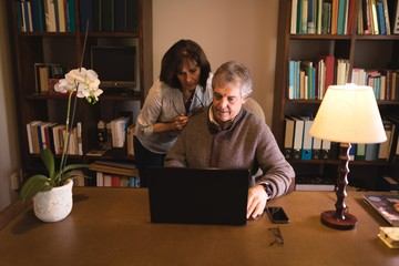 Couple using using laptop at desk