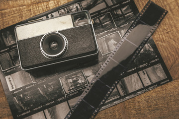 Old analog camera, film and contact sheet over wooden table.