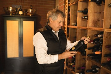 Senior man holding wine bottle