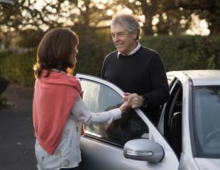 Senior couple holding hands near the car