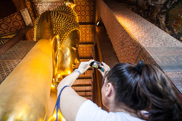Tourist with smartphone taking a photo of giant Buddha in Bangkok