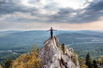 Foto auf AluDibond Himmelblau A young man on a mountain peak. Hands to both sides. Concept of freedom and absence of limitations. South Urals. Alexandrovskaya Sopka.