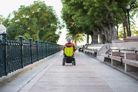 Mulher sentada em uma cadeira de rodas e desfrutar do ar livre