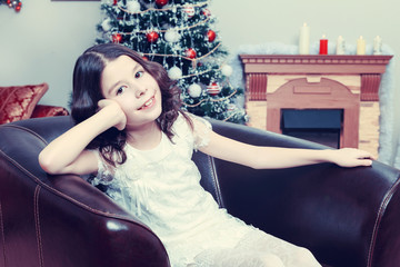 The little girl in the armchair by the Christmas tree.