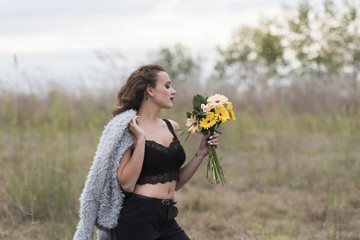 Young pretty woman with curly long hair holding a bouquet of flowers, outdoor shoot with cloudy sky