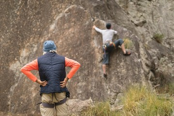 Man looking at his friend while climbing mountain