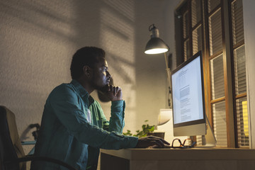 Creative black man using computer at late afternoon.