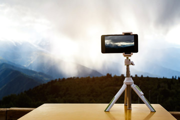 smartphone on a tripod in the mountains, a storm against the background.