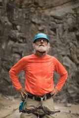 Senior man wearing safety equipment during mountaineering