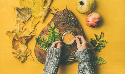 Autumn morning coffee concept. Flat-lay of woman' s hands in grey woolen sweater holding cup of espresso over mustard yellow background with dried fallen leaves and fresh pomegranates around, top view