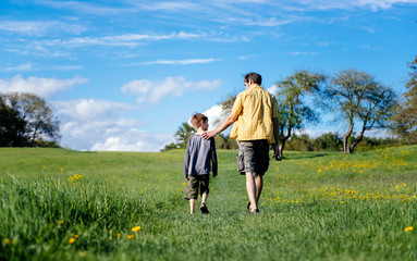 Father and son walk together in a field on a beautiful spring day
