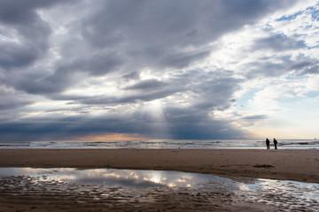 Sunshine beams shining through dark rain clouds over the ocean