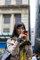 Young chinese couple taking photos on their phones in city street
