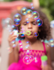 Portrait of a young girl with curly hair blowing colorful bubbles