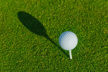 Golf ball on the green course. Close up. Sport, relax, recreation and leisure concept