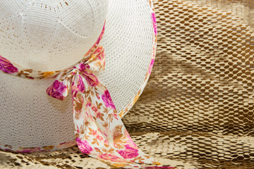 white hat with a flowered ribbon