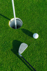 Golf club and ball on the green course. Close up. Top view. Sport, relax, recreation and leisure concept